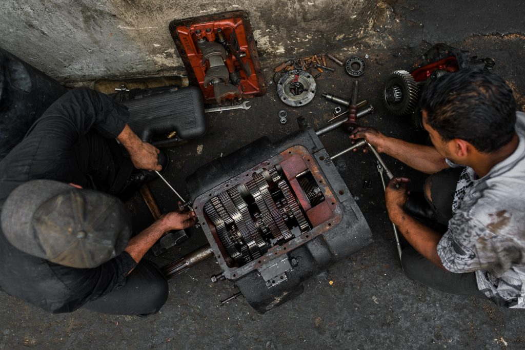 Colombian car mechanics work on a transmission in a car