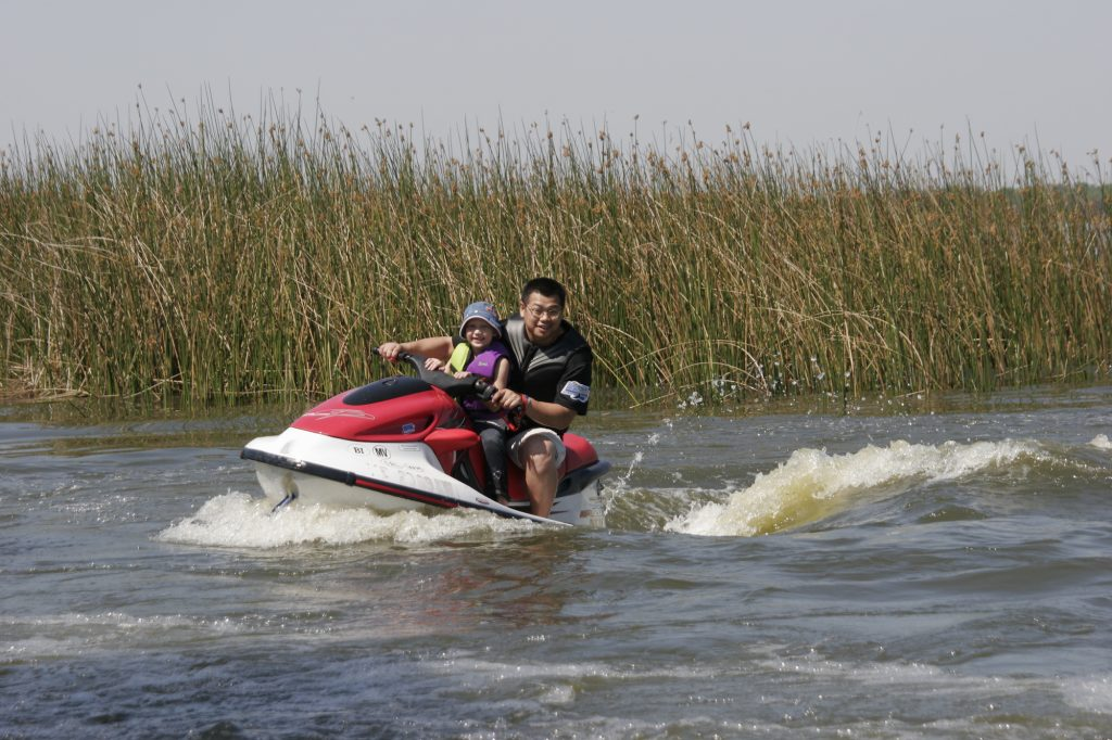 A man and a child ride a waverunner on Lake Parker in Lakeland, Florida