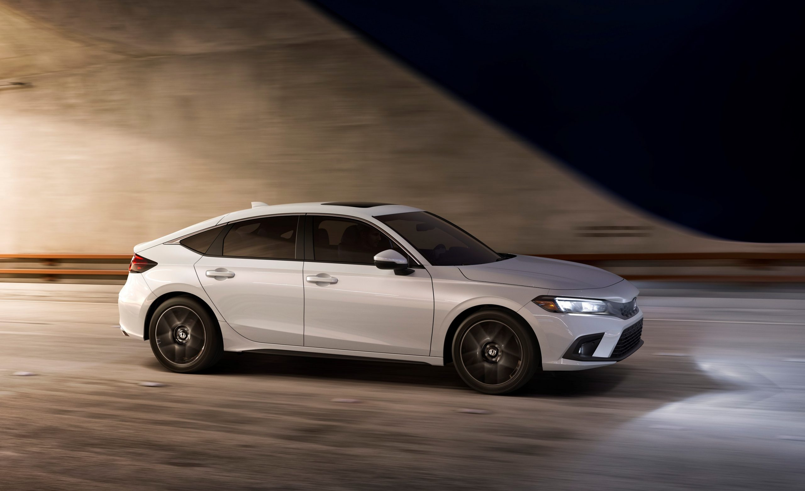 A white 2022 Honda Civic hatch photographed in a tunnel, shot in profile