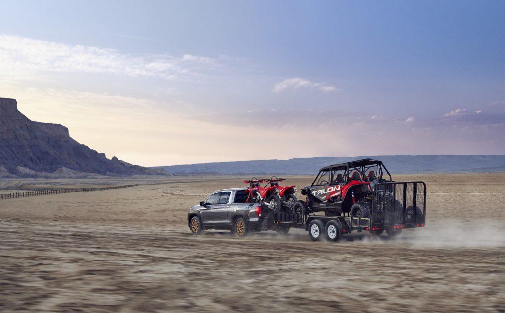 2021 Honda Ridgeline HPD towing two dirt bikes and a UTV through the desert