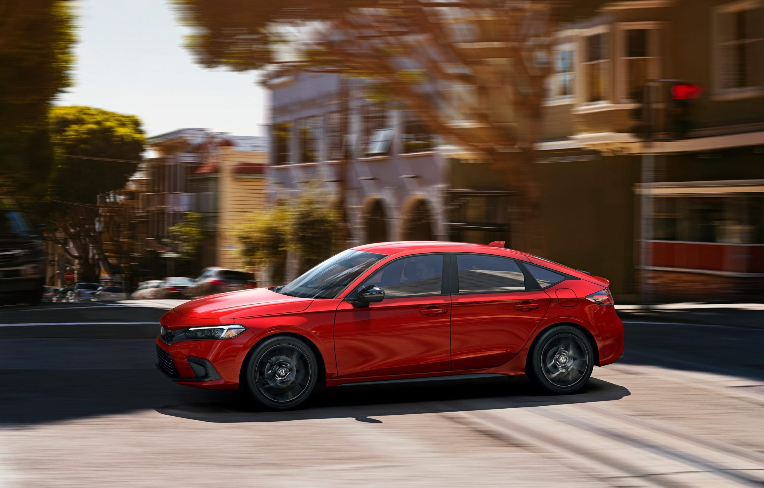 A red 2022 Honda Civic hatchback shot in profile on a city street