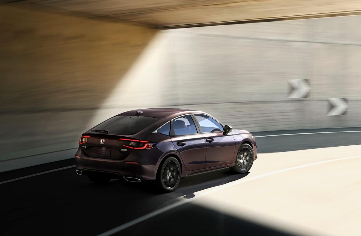Honda civic hatchback driving under an overpass