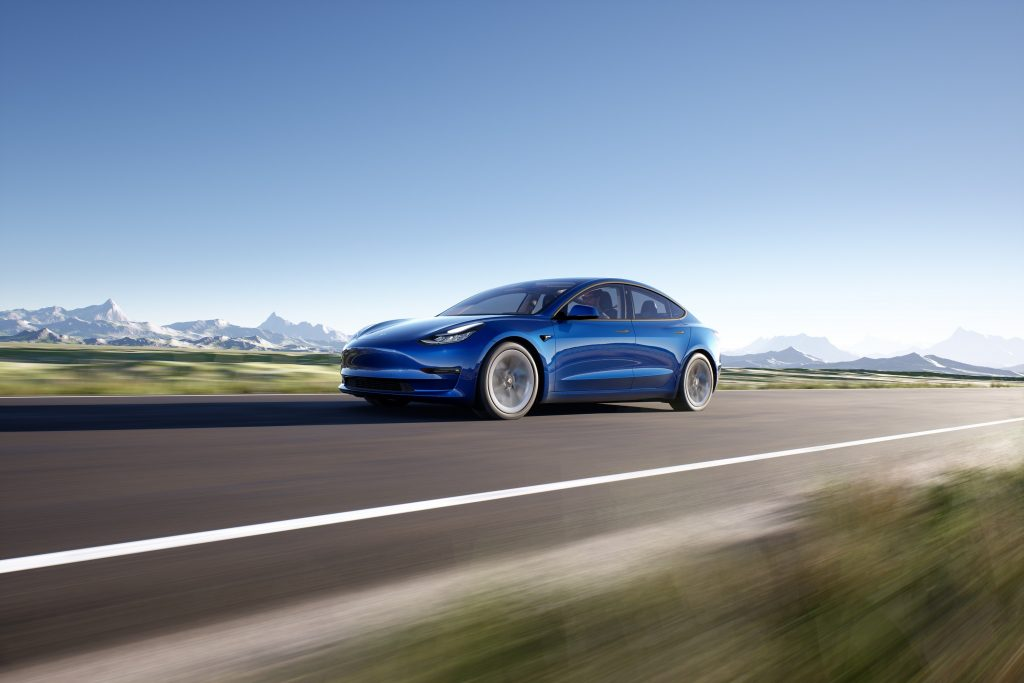 A blue Tesla Model 3 blasts it's way down a picturesque open road with mountains in the background
