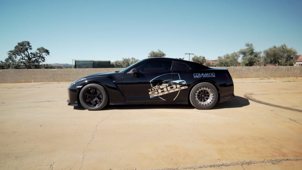 """""""Dancing Dan"""" Rue's 1,400 horsepower 2017 Nissan GT-R drag race car. The car is black with thick sidewall tires. There is a chrome graphic on the side of the car that reads """"The SHOP Houston"""""""