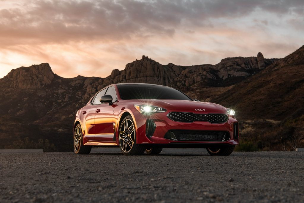 A red 2022 Kia Stinger shot at sunset from the lower front 3/4 angle