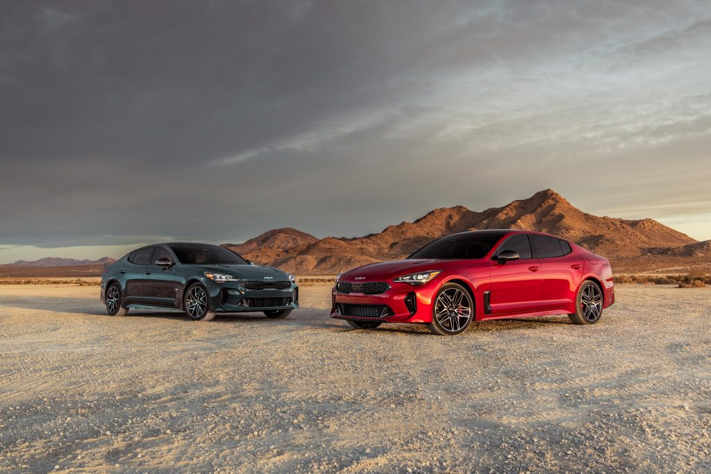 A red 2022 Kia Stinger GT and a Stinger GT-line photographed on in the desert together from the front 3/4 angle