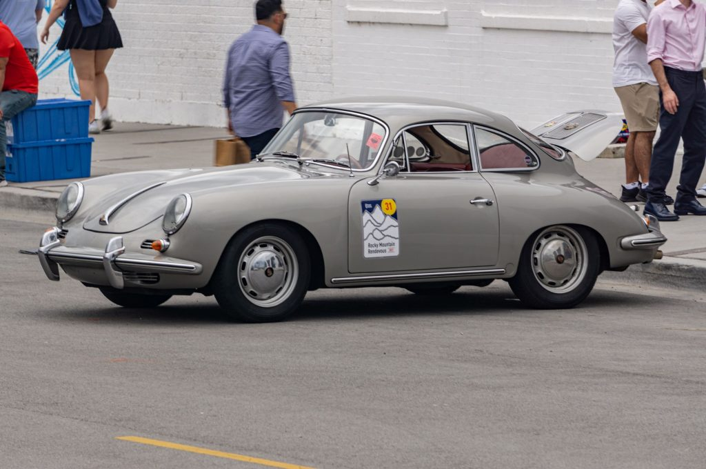The side 3/4 view of a gray 1961 Porsche 356B 1600 Super 90 parked on the street