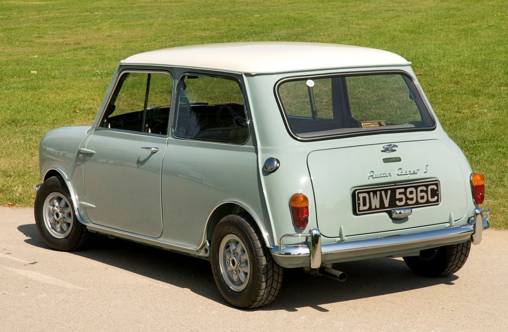 The rear 3/4 view of a light-green-and-white 1965 Austin Mini Cooper S