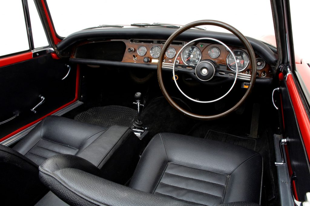 The black-leather-upholstered seats and wood-trimmed dashboard of a red British-market 1965 Sunbeam Tiger MKI