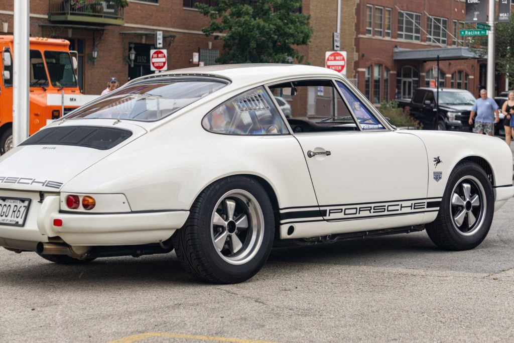 The rear 3/4 view of a white-and-black 1967 Porsche 911R on the Checkeditout parking lot