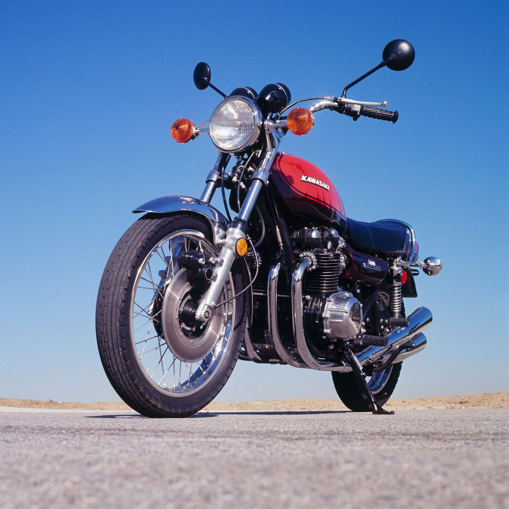 A low-angle front 3/4 view of an orange-and-black 1973 Kawasaki Z1 900 on a desert runway