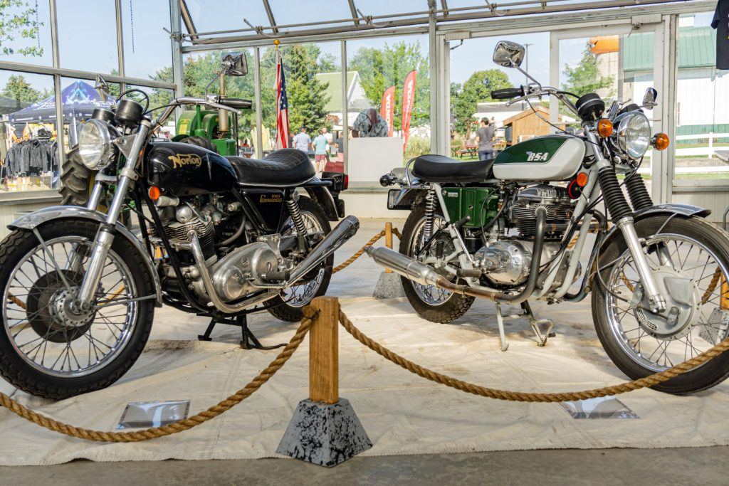 A black-and-gold 1974 Norton Commando 850 to the left of a green-and-white 1971 BSA A65 Thunderbolt at IMS Outdoors Chicago 2021