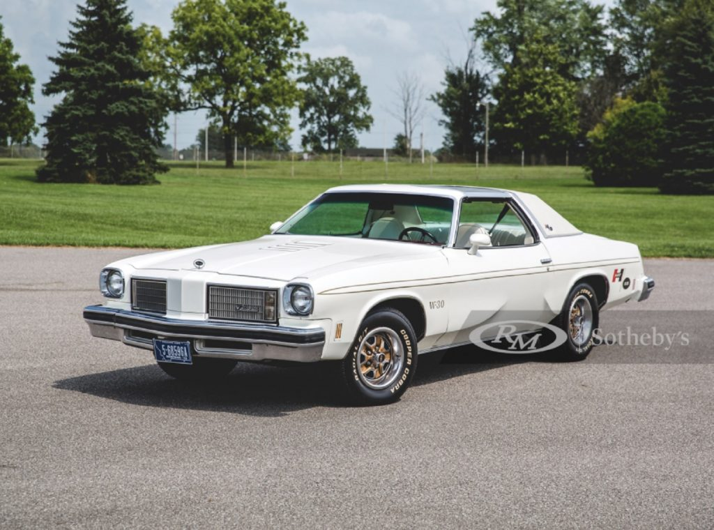 A white-and-gold 1975 Oldsmobile Cutlass Supreme Hurst/Olds W-30 in a parking lot