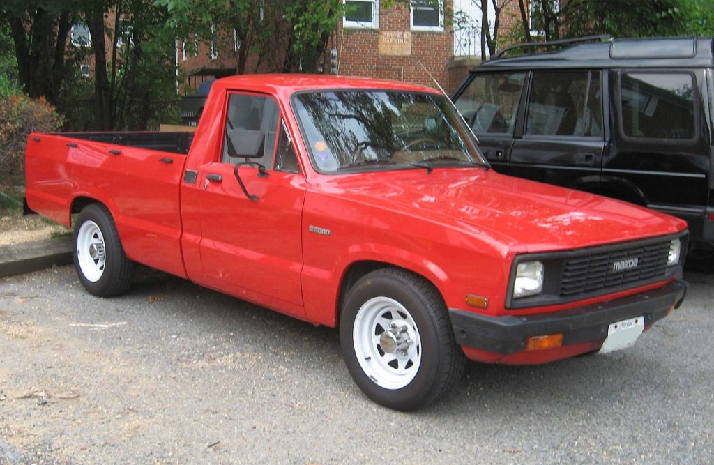 A red 1977 Mazda B-Series parked outside