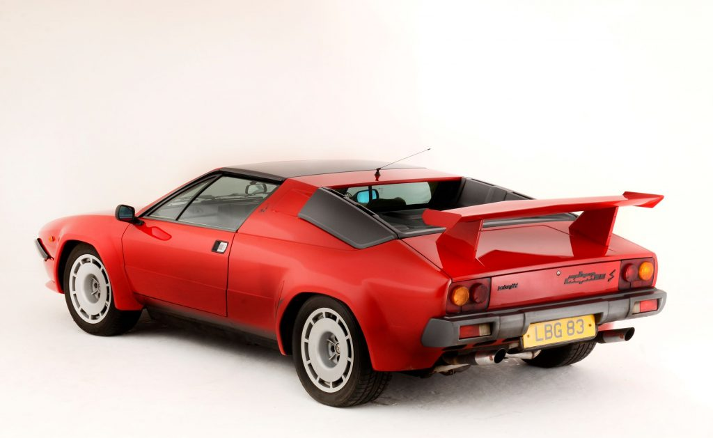 The rear 3/4 view of a red 1984 Lamborghini Jalpa S with a rear spoiler