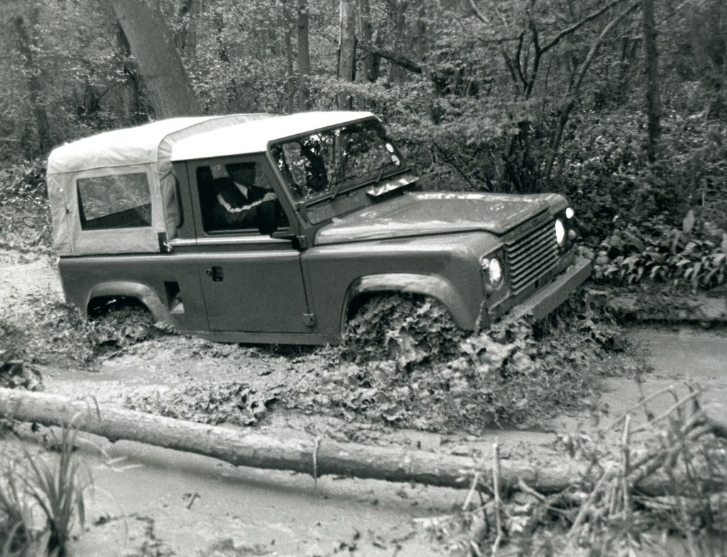A 1984 Land Rover 'Defender' 90 off-roading through a muddy forest river