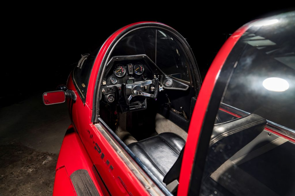 The dashboard and front seat of a red 1985 Pulse Litestar Autocycle with its canopy open