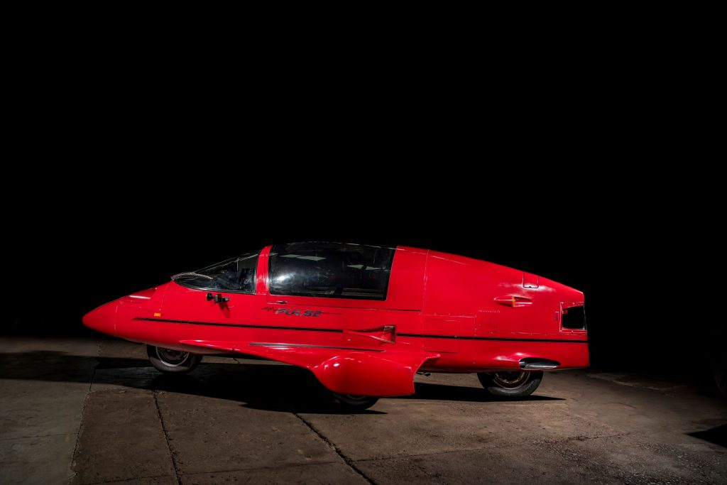 The side 3/4 view of a red 1985 Pulse Litestar Autocycle
