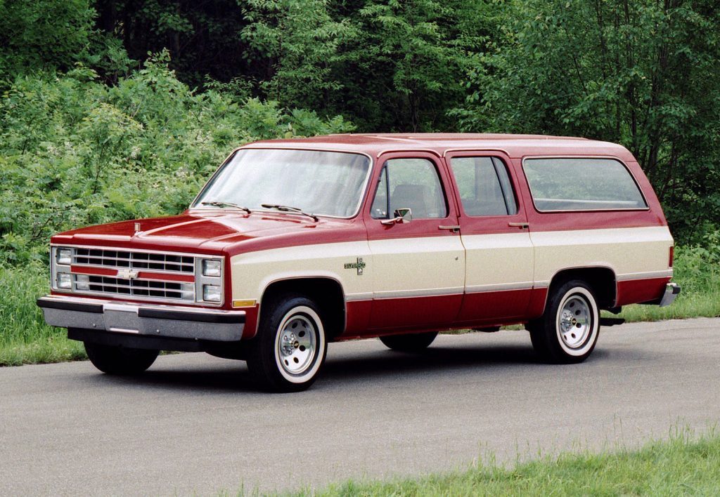 This is a vintage promotional photo of a two-tone 1985 Chevrolet Suburban.  In Cry Macho, Clint Eastwood character drives a similar Chevrolet Suburban in Mexico |  General Motors