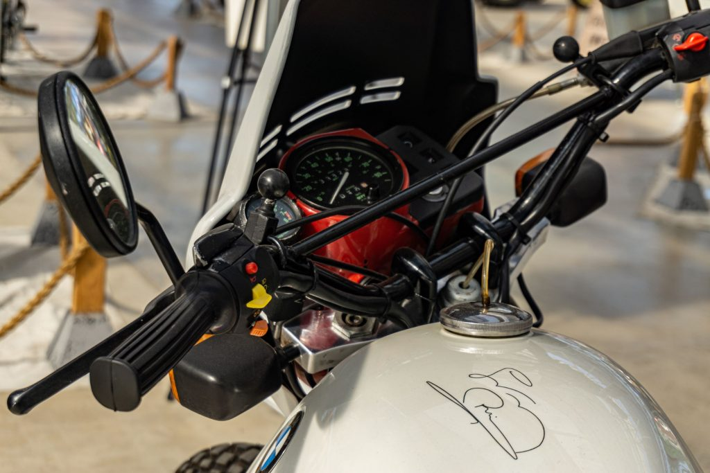 A close-up view of a white 1987 BMW R80 G/S's handlebars, autographed fuel tank, and red-trimmed gauges