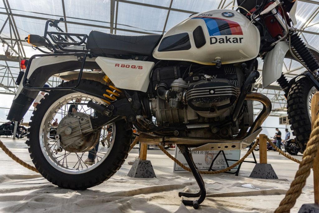A low-angle side view of a white-black-red-and-blue 1987 BMW R80 G/S Paris Dakar's rear half and engine