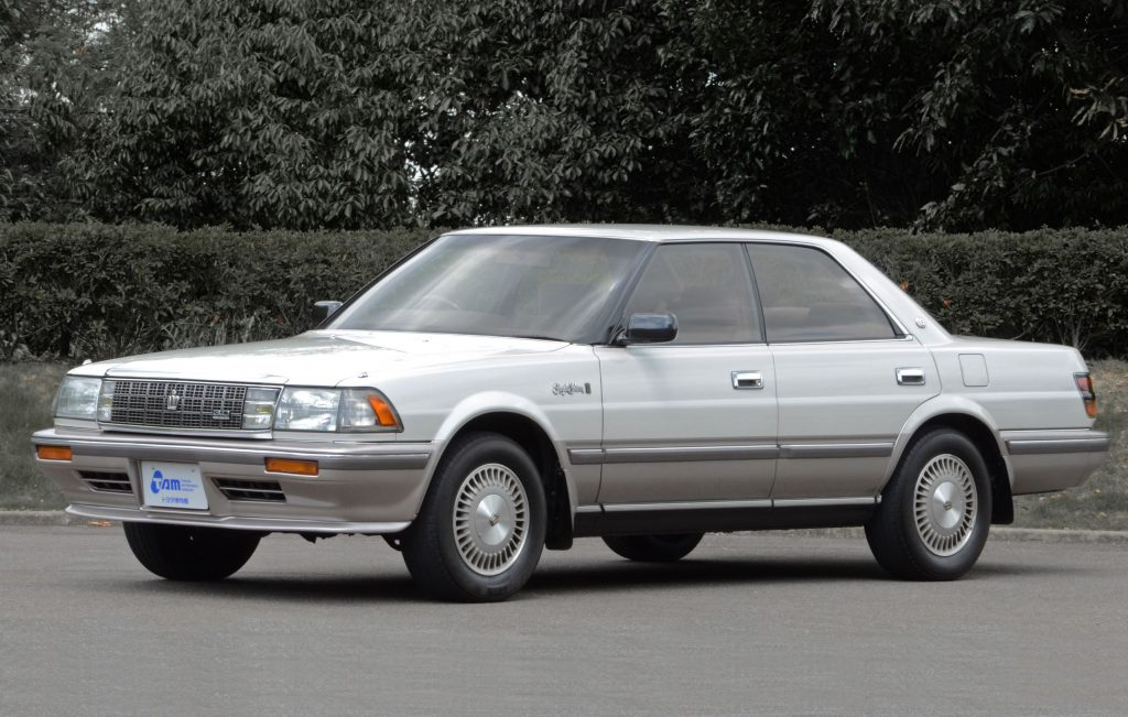 A white-and-gray 1988 Toyota 'S130' Crown Royal Saloon
