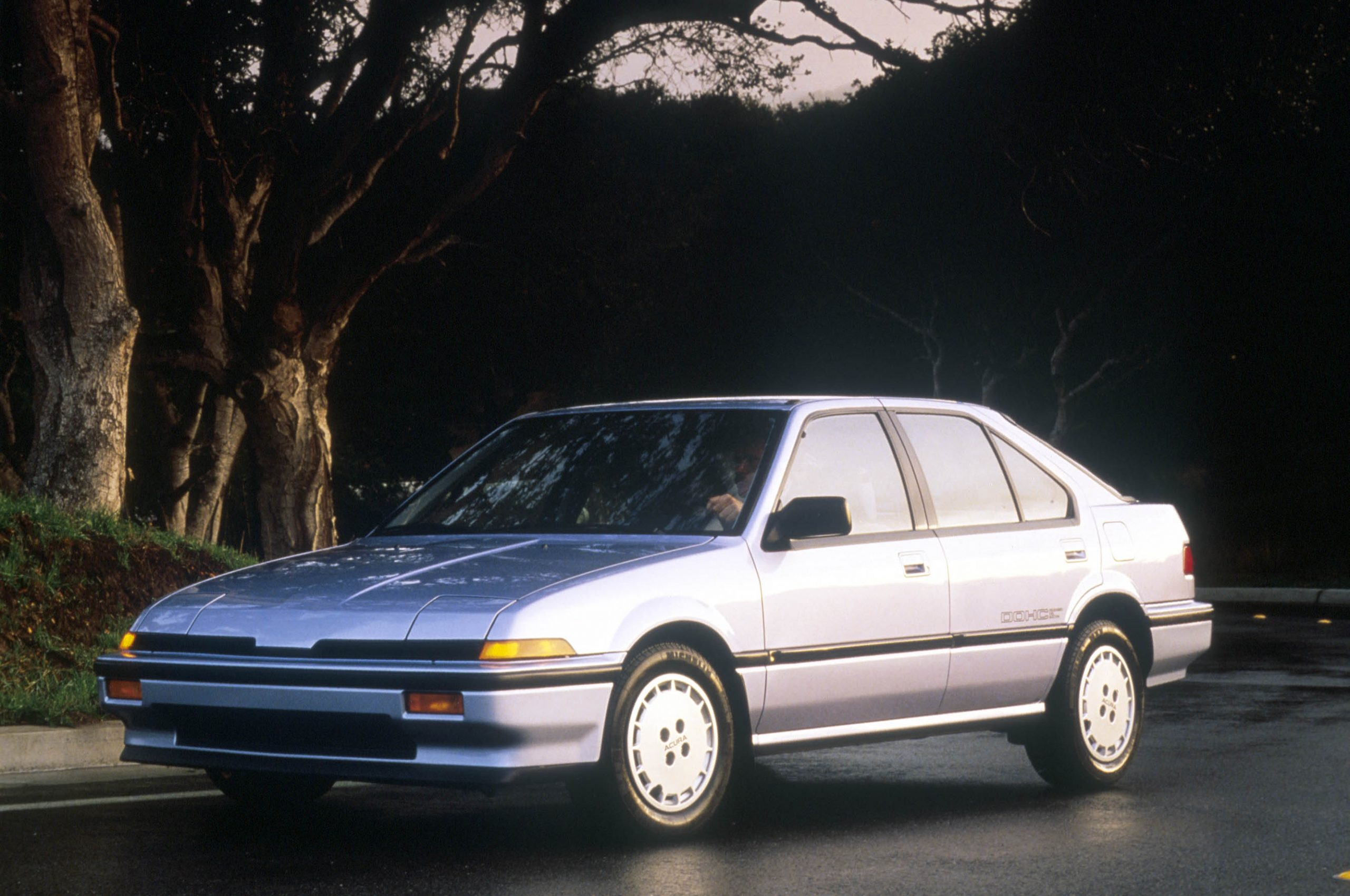 A silver 1986 Acura Integra RS shot from the 3/4 angle on a wet city street