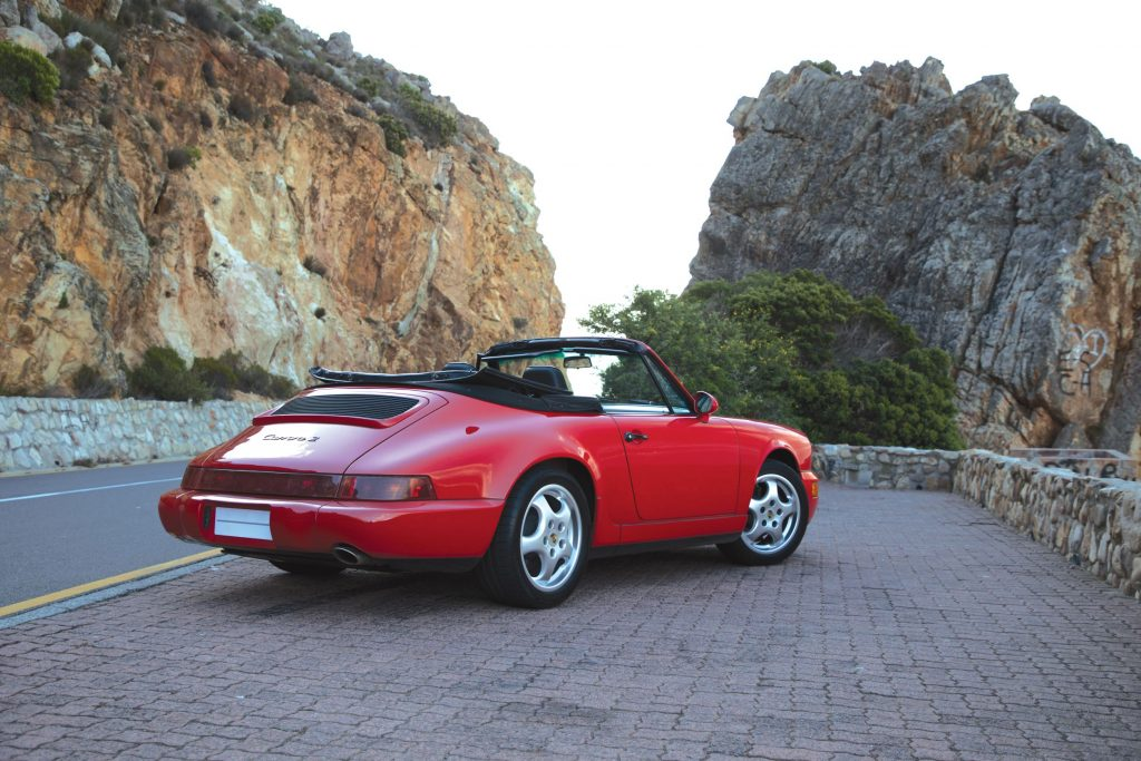 The rear 3/4 view of a red 1990 964 Porsche 911 Carrera 2 Cabriolet on a South African mountain road