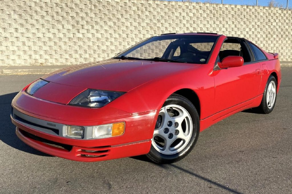 A red 1990 Nissan 300ZX Twin Turbo parked by a stone wall