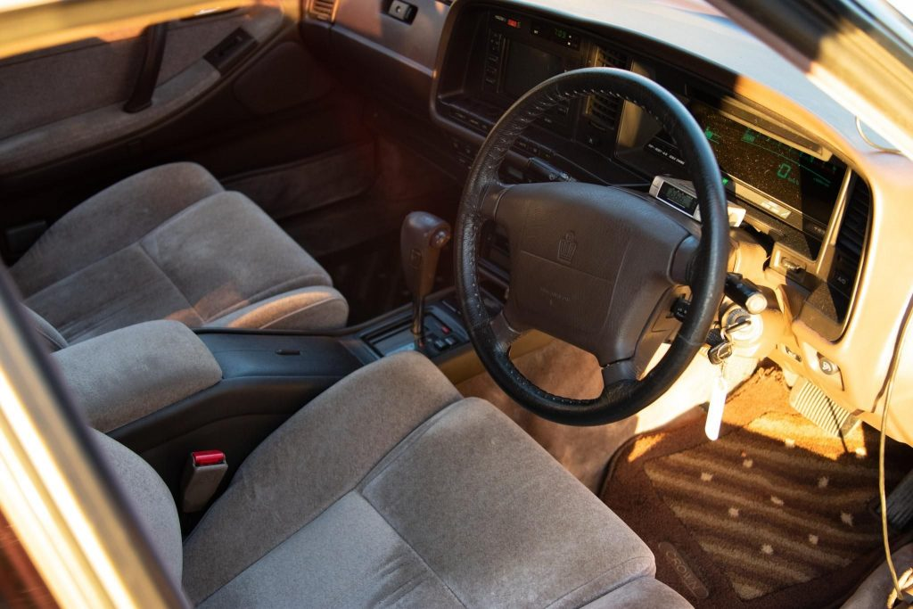The brown-gray-velour-upholstered front seats and brown dashboard of a JDM 1991 Toyota Crown
