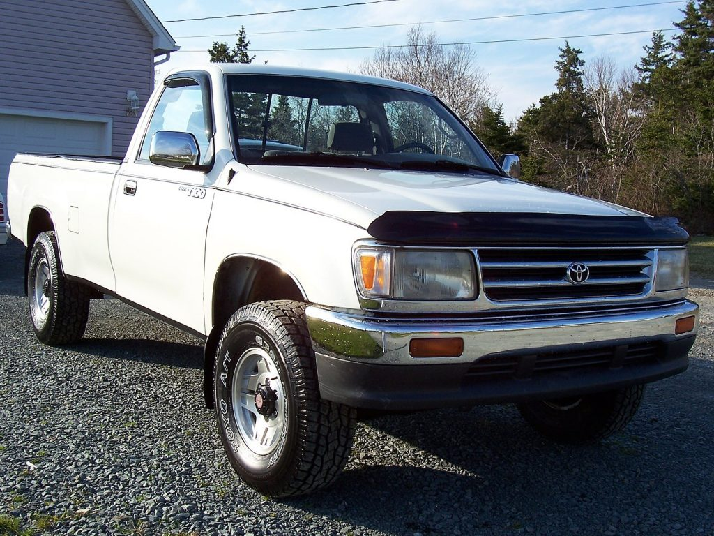 A white 1993 Toyota T100 is parked outside