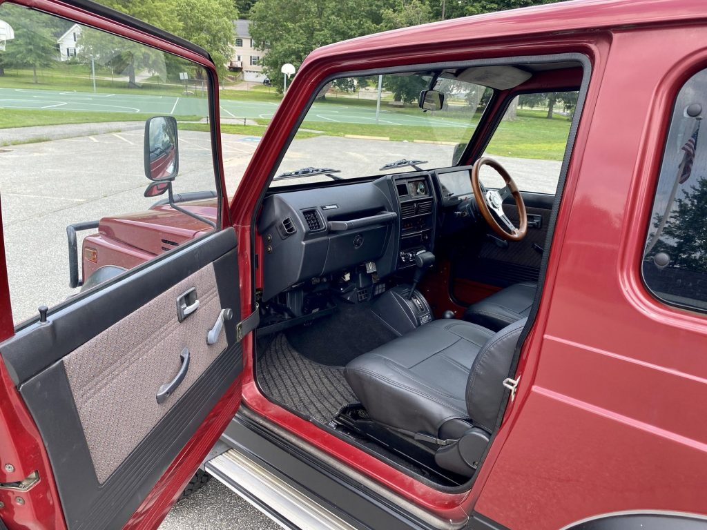 The side view of a red 1994 Suzuki Jimny Sierra 4x4's interior with leather seat covers