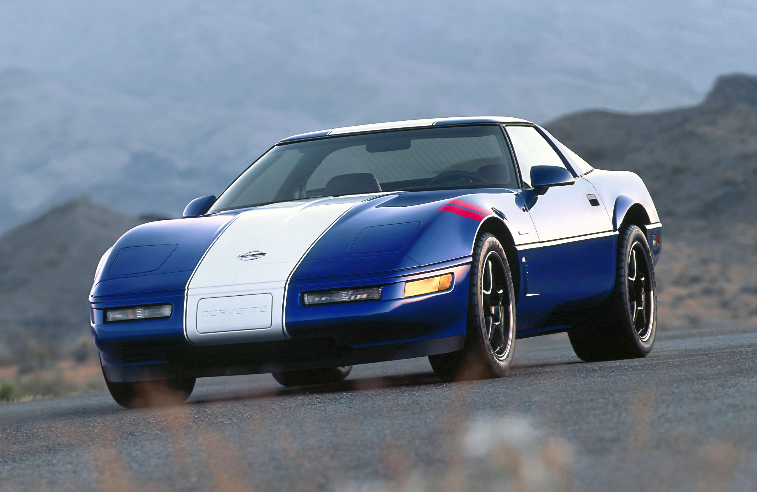 A blue and white-striped Chevy Corvette C4 Grand Sport shot from the front 3/4 angle