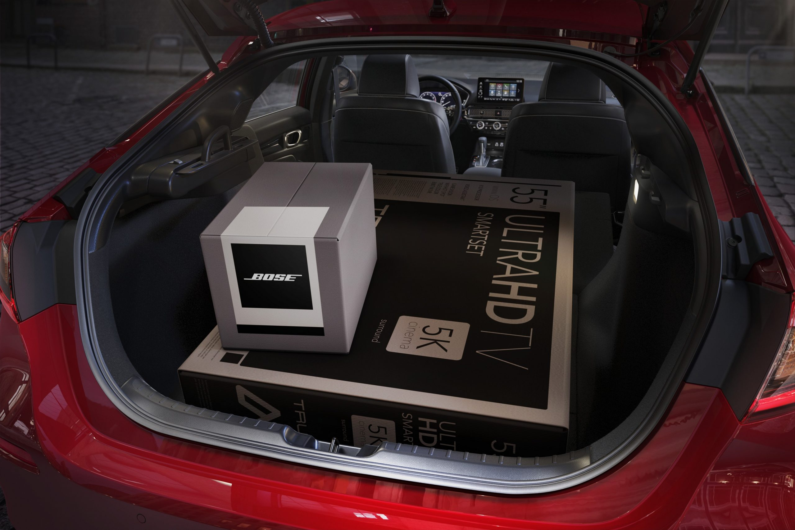 The cavernous rear hatch of the 2022 Honda Civic filled with a large TV and Bose speaker