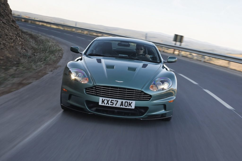 This is a publicity photo of a green Aston Martin DBS V12 grand tourer driving down the highway. This is one car both James Bond and Jay Leno own.
