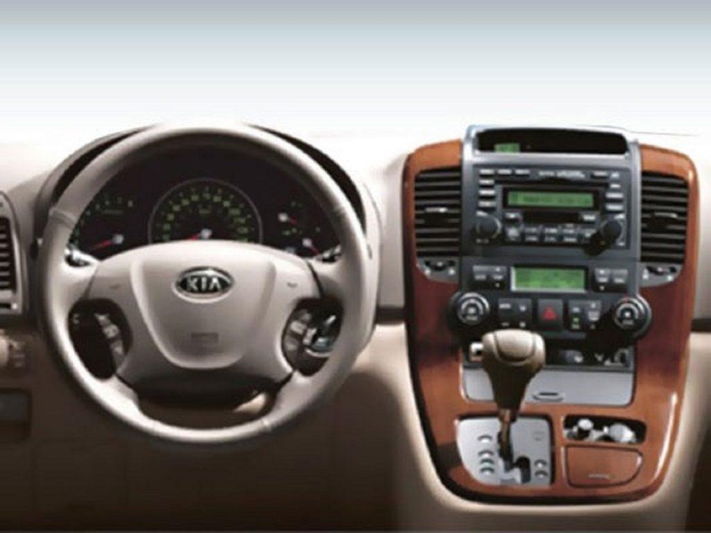 The steering wheel and shifter inside a 2008 Kia Sedona.