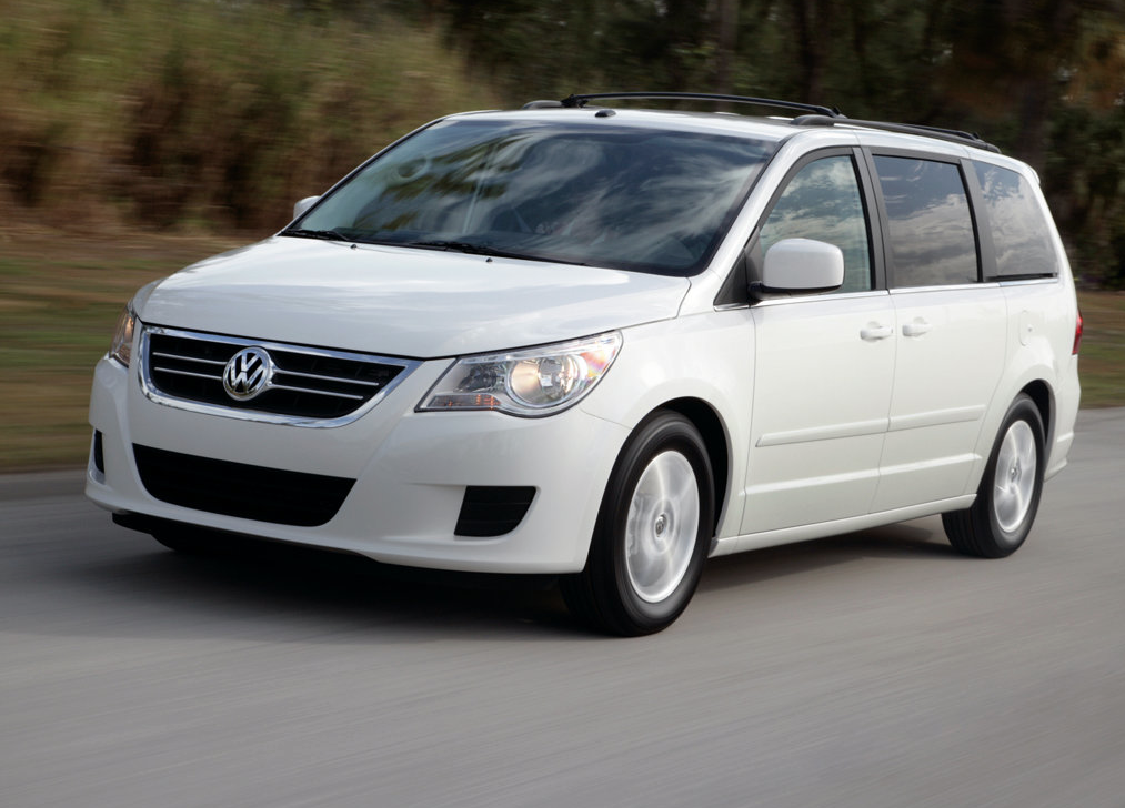 A white 2009 volkswagen routan drives on a road during the day