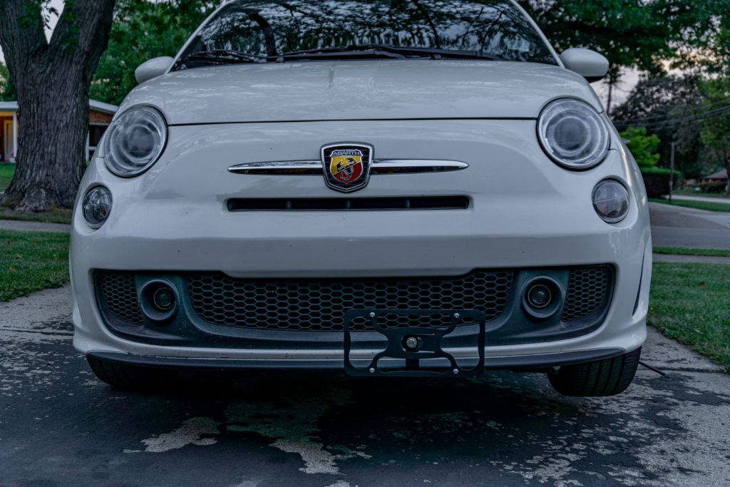 A white 2013 Fiat 500 Abarth with a black CravenSpeed Platypus front license plate holder