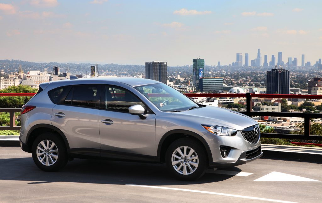 A silver 2014 Mazda CX-5 parked on a road overlooking a city skyline