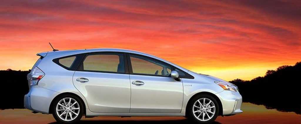 A 2014 Toyota Prius in front of a sunset and water