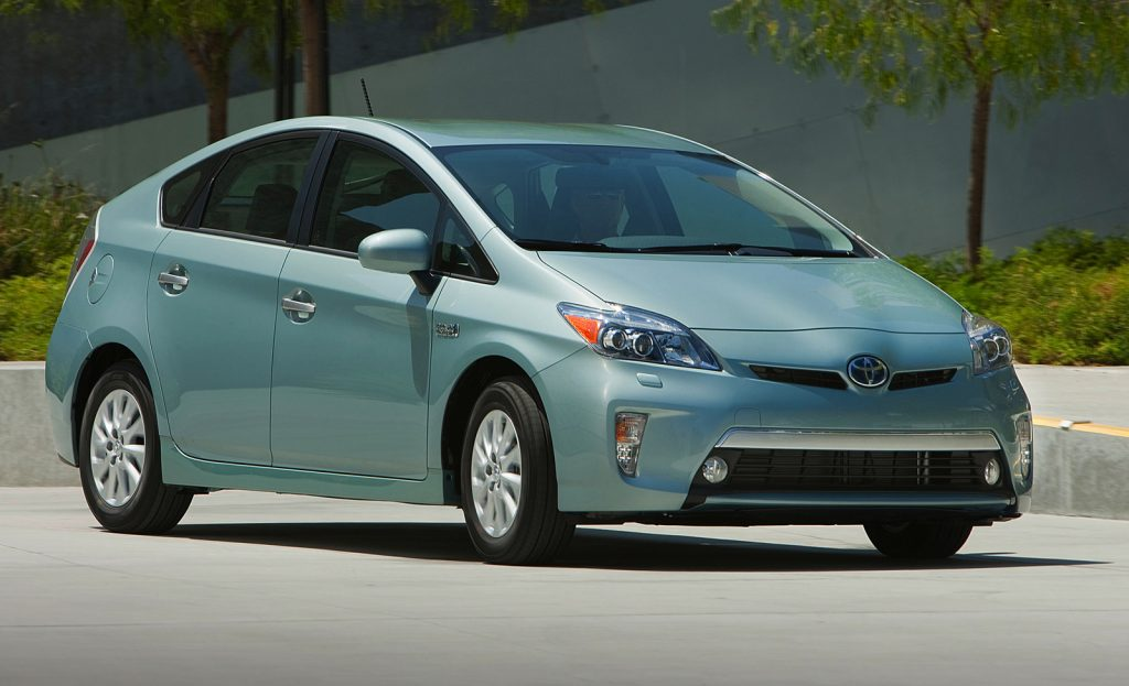 A green 2014 Toyota Prius Plug-In Hybrid drives on a road