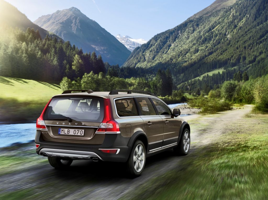 A bronze 2014 Volvo XC70 wagon traveling on a dirt road along a river through a mountain valley
