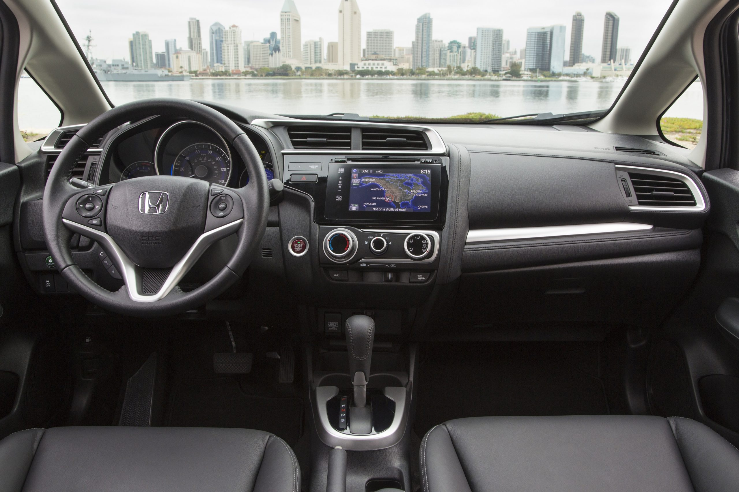 The interior of the 2015 Honda Fit with a conventional layout featuring the infotainment and climate control settings in the middle of the car