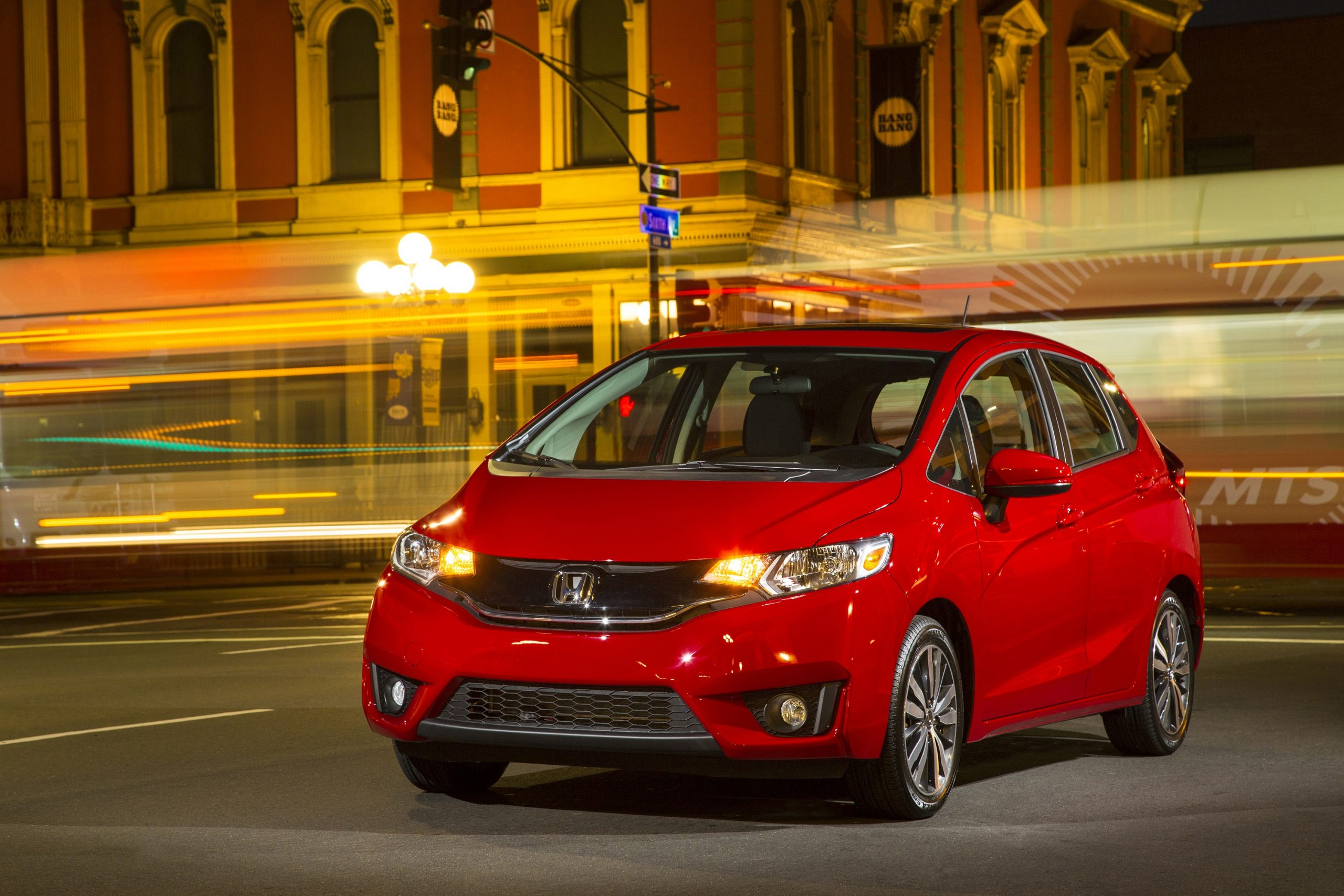 A red 2015 Honda Fit shot on a long exposure setting at night, making the traffic behind blur