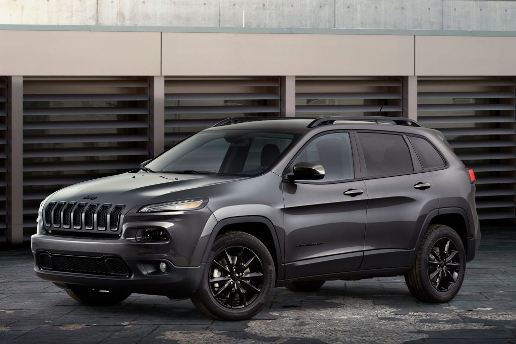 A gray 2015 Jeep Cherokee parked outside by a wall