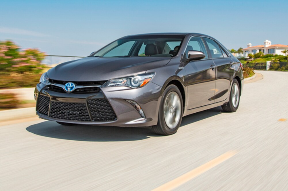 A grey 2015 Toyota Camry Hybrid driving on a sunny day