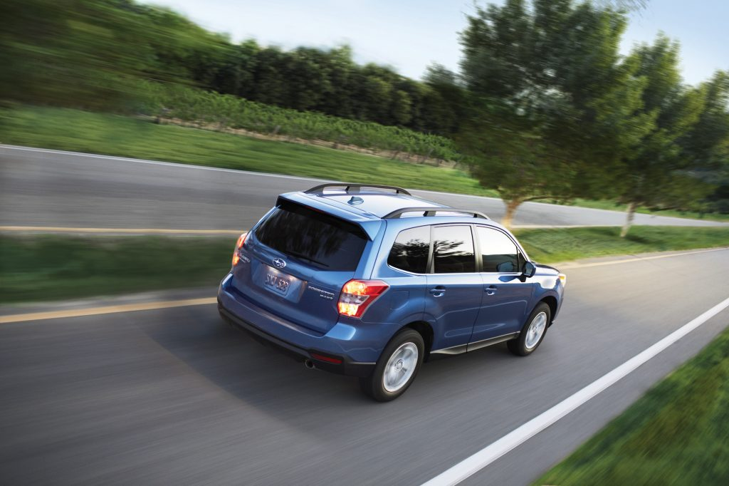 A blue metallic 2016 Subaru Forester 2.5i travels on a road with a grassy medium dotted with trees