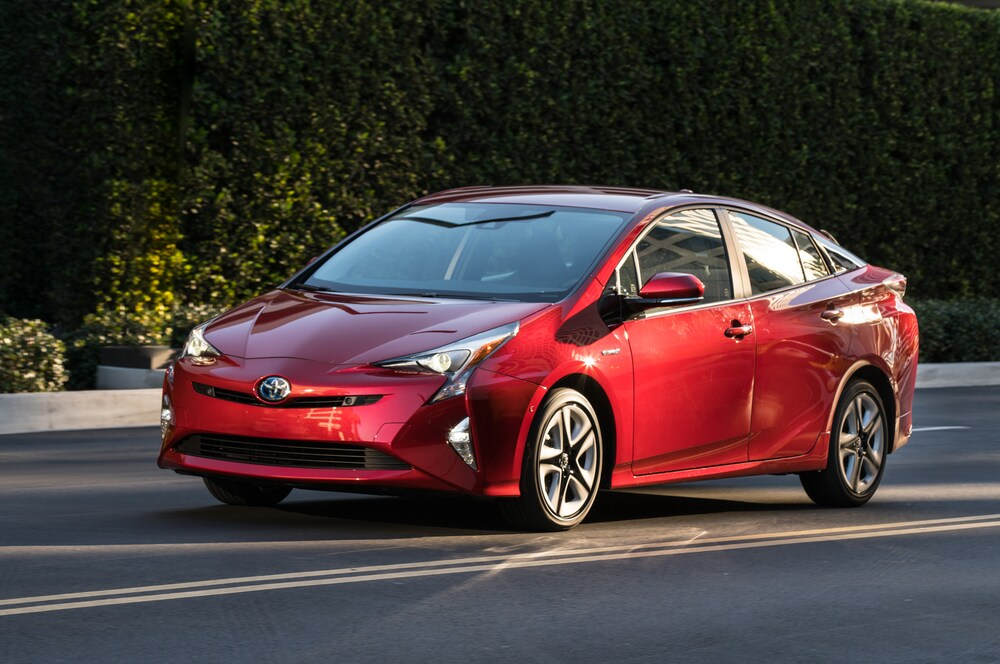 A red 2016 Toyota Prius Hybrid driving on a road