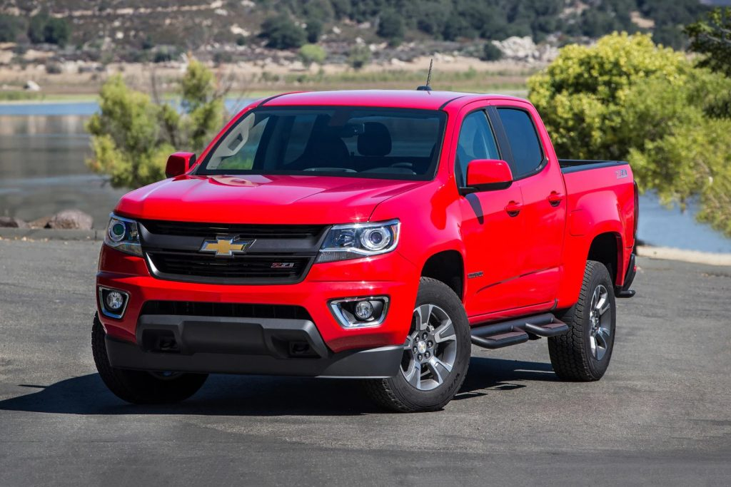 A red 2017 Chevrolet Colorado parked by water - one of the best used pick up trucks under $20,000