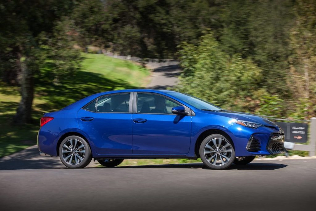 A blue 2017 Toyota Corolla SE traveling on a country road surrounded by green hills and trees
